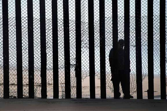 """(FILES) This file photo taken on February 13, 2017 shows  a man standing on the Mexico side of a border fence separating the beaches at Border Field State Park, in San Diego, CA.  Some Hispanic business owners in the United States are offering to help build President Donald Trump's wall to keep out unauthorized immigrants on the Mexican border, despite controversy and their personal misgivings.""""Myself, being an Hispanic makes it tougher,"""" Michael Luera, who runs a construction services firm in Ganado, Texas, told AFP.His company, Fairfield Logistics, recently expressed interest in working on the border wall project, which has become a lightning rod for public outrage in the debate over Trump's immigration policies. But it was not an easy choice.   / AFP PHOTO / JIM WATSONJIM WATSON/AFP/Getty Images"""