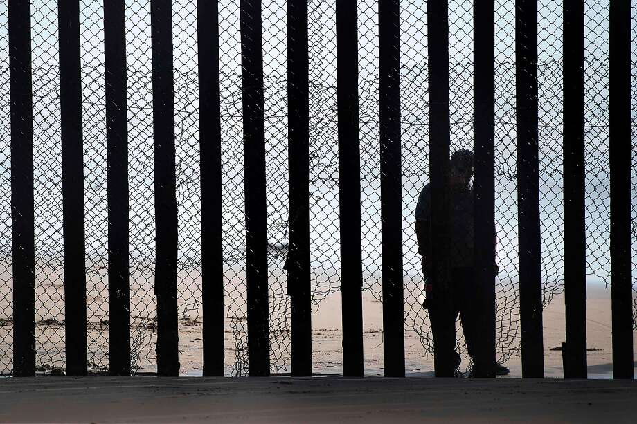 A man standing on the Mexico side of a border fence separating the beaches at Border Field State Park, in San Diego. Some Hispanic business owners in the United States are offering to help build President Donald Trump's wall to keep out unauthorized immigrants on the Mexican border, despite controversy and their personal misgivings. Photo: JIM WATSON, AFP/Getty Images