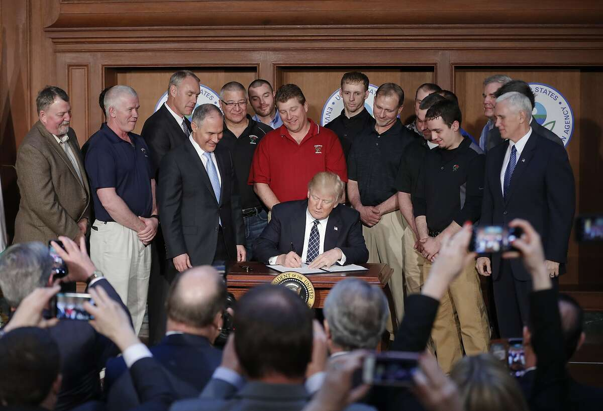 President Donald Trump, accompanied by Environmental Protection Agency (EPA) Administrator Scott Pruitt, third from left, and Vice President Mike Pence, right, signs an Energy Independence Executive Order, Tuesday, March 28, 2017, at EPA headquarters in Washington. (AP Photo/Pablo Martinez Monsivais)