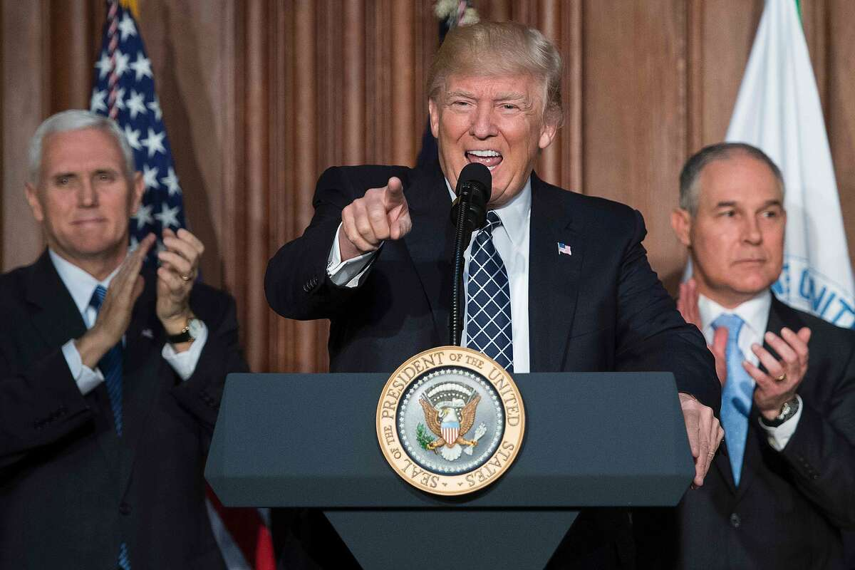 """US President Donald Trump (C) speaks before signing the Energy Independence Executive Order at the Environmental Protection Agency (EPA) Headquarters in Washington, DC, March 28, 2017, with Vice President Mike Pence (L) and Environmental Protection Agency Administrator Scott Pruitt (R). President Donald Trump claimed an end to the """"war on coal"""" Tuesday, as he moved to roll back climate protections enacted by predecessor Barack Obama. / AFP PHOTO / JIM WATSONJIM WATSON/AFP/Getty Images"""