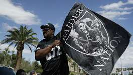 Ken Mclin holds up a Raiders banner on March 27, 2017, in Las Vegas. NFL team owners approved the move of the Raiders to Las Vegas in a vote at an NFL annual meeting in Phoenix.