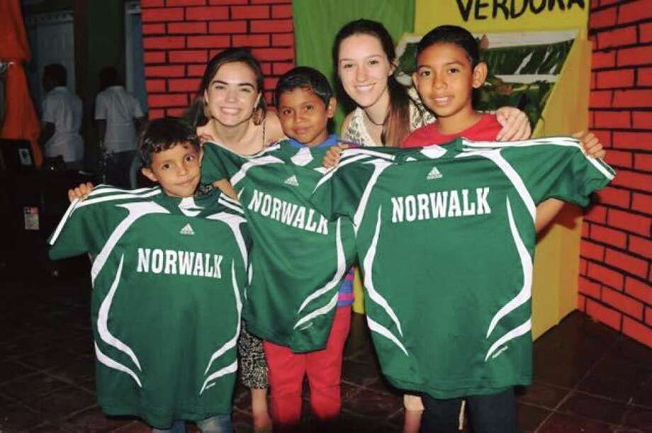 Norwalk High seniors Grace Bradley, rear left, and classmate Sabrina Imbrogno, rear right, pose for a photo with some young soccer players from Nagarote, Nicaragua, who received a donation of Norwalk High soccer uniforms courtesy of the school's athletic department during a recent trip. Photo: Contributed Photo / Hearst Connecticut Media / Norwalk Hour
