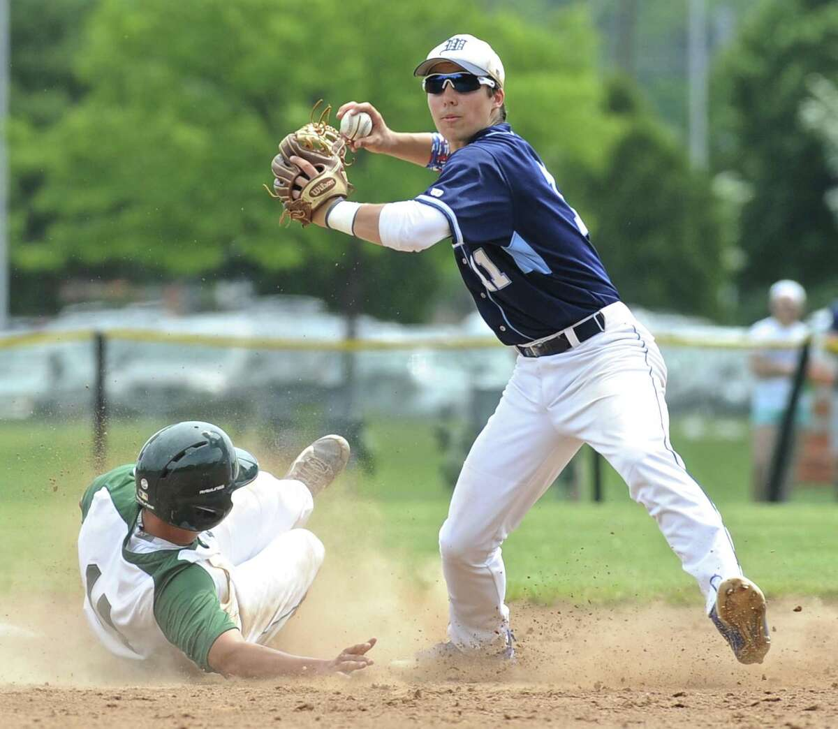 Wilton's Collin Kahal looks to throw to first after putting out New Milford's Tyler Hansen at second in a Class LL quarterfinal game June 4.
