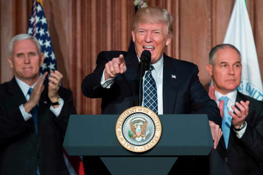 """US President Donald Trump (C) speaks before signing the Energy Independence Executive Order at the Environmental Protection Agency (EPA) Headquarters in Washington, DC, March 28, 2017, with Vice President Mike Pence (L) and Environmental Protection Agency Administrator Scott Pruitt (R). President Donald Trump claimed an end to the """"war on coal"""" Tuesday, as he moved to roll back climate protections enacted by predecessor Barack Obama. / AFP PHOTO / JIM WATSONJIM WATSON/AFP/Getty Images Photo: JIM WATSON, Staff / AFP or licensors"""