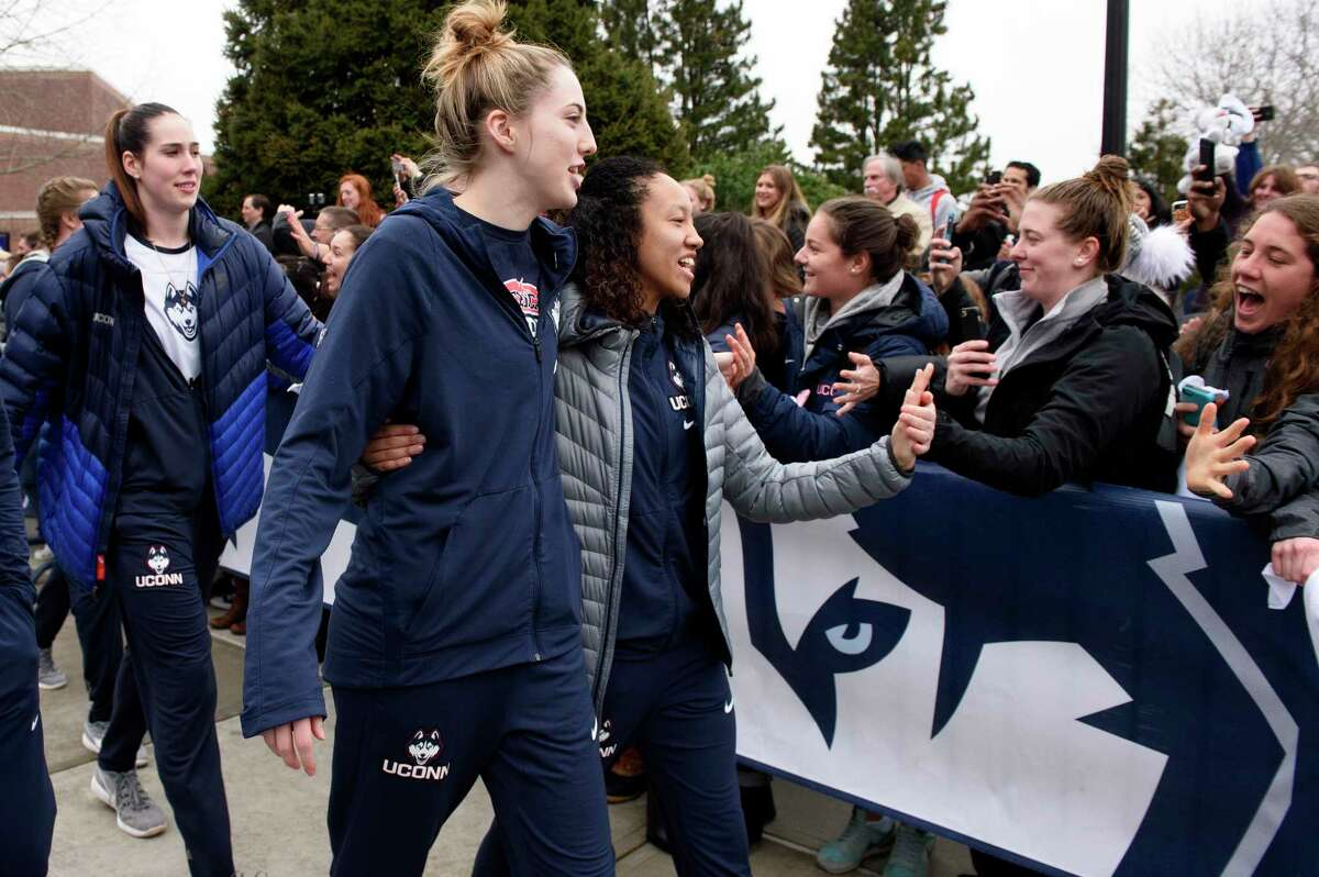 Connecticut basketball players Katie Lou Samuelson, front left, and Saniya Chong greet fans outside Gampel Pavilion in Storrs, Conn., Tuesday, March 28, 2017 as they prepare to board a bus to depart for the Final Four of the NCAA college basketball tournament in Dallas. UConn's Natalie Butler, rear left, follows. (Mark Mirko/Hartford Courant via AP) ORG XMIT: CTHAR201