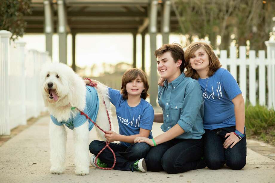 Will Herndon, center, with his brothers Magnus and Steele, along with family dog Buster. The 8th annual HOPE On the Green is on April 10 at The Woodlands Country Club Palmer Course. Funds benefits research for Batten disease. Photo: Kelly Schafler