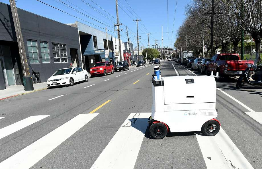 A robot, made by the startup Marble, rolls across a street in San Francisco. Delivery robots, would be banned from San Francisco sidewalks under legislation Supervisor Norman Yee was introducing on Tuesday. Photo: Susana Bates, Special To The Chronicle