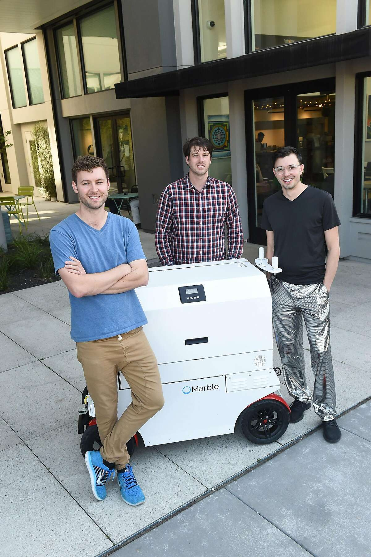From left: Matt Delaney, Kevin Peterson and Jason Calaiaro, pose for a photo in front of one of their robots on March 28, 2017. They are co-founders of the start up company Marble which makes robots to deliver food and other items.