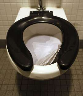 A toilet is filled with seat covers left behind at the men's restroom at San Francisco's main library on Tuesday Oct. 1, 2013, in San Francisco, Calif. The bathrooms become so dirty a custodian cleans up every twenty minutes throughout the day.