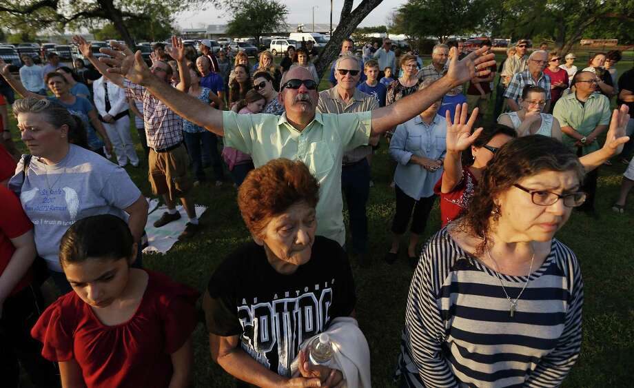 Joel McLeod extends his arms in prayer as he joins others from La Vernia at a prayer service at the city park. Photo: Kin Man Hui /San Antonio Express-News / ©2017 San Antonio Express-News