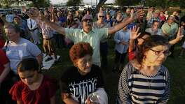 Joel McLeod extends his arms in prayer as he joins others from La Vernia at a prayer service at the city park.