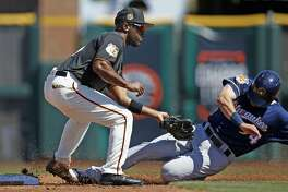 Milwaukee Brewers center fielder Kyle Wren, right, is tagged out by San Francisco Giants shortstop Jimmy Rollins, as Wren tries to steal second base during the second inning of a spring training baseball game, Sunday, March 19, 2017, in Scottsdale, Ariz. (AP Photo/Ross D. Franklin)