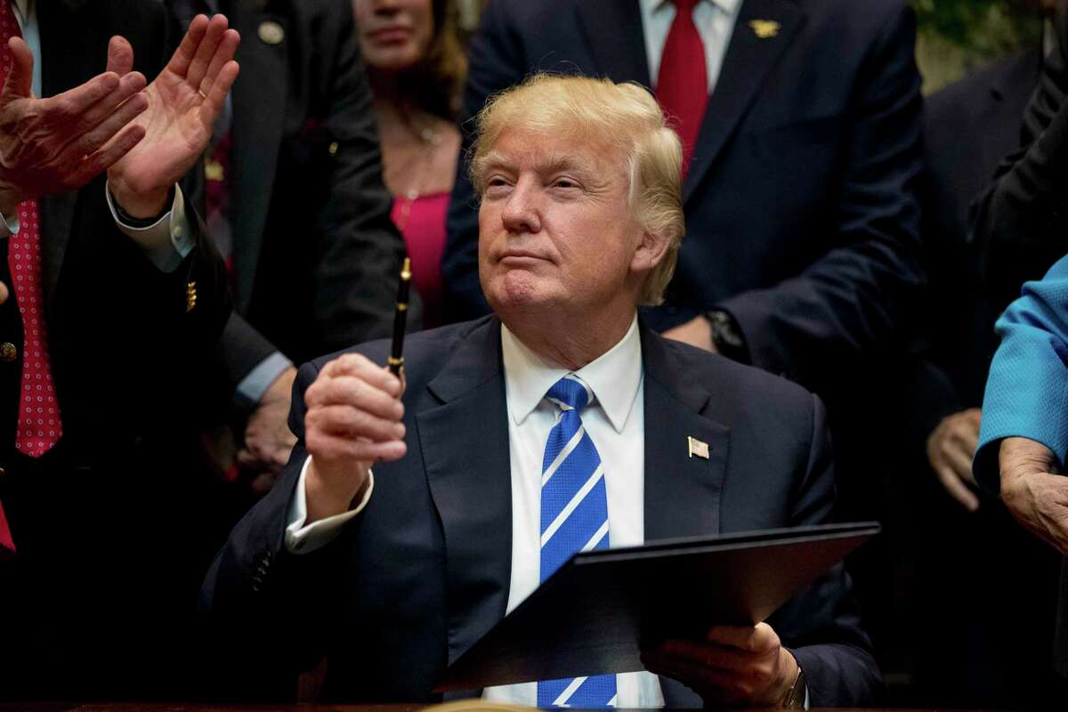 FILE - In this Monday, March 27, 2017, file photo, President Donald Trump holds up a pen he used to sign one of various bills in the Roosevelt Room of the White House in Washington. Ignoring fresh threats from the White House, city leaders across the U.S. are vowing to intensify their fight against Trump's promised crackdown on so-called