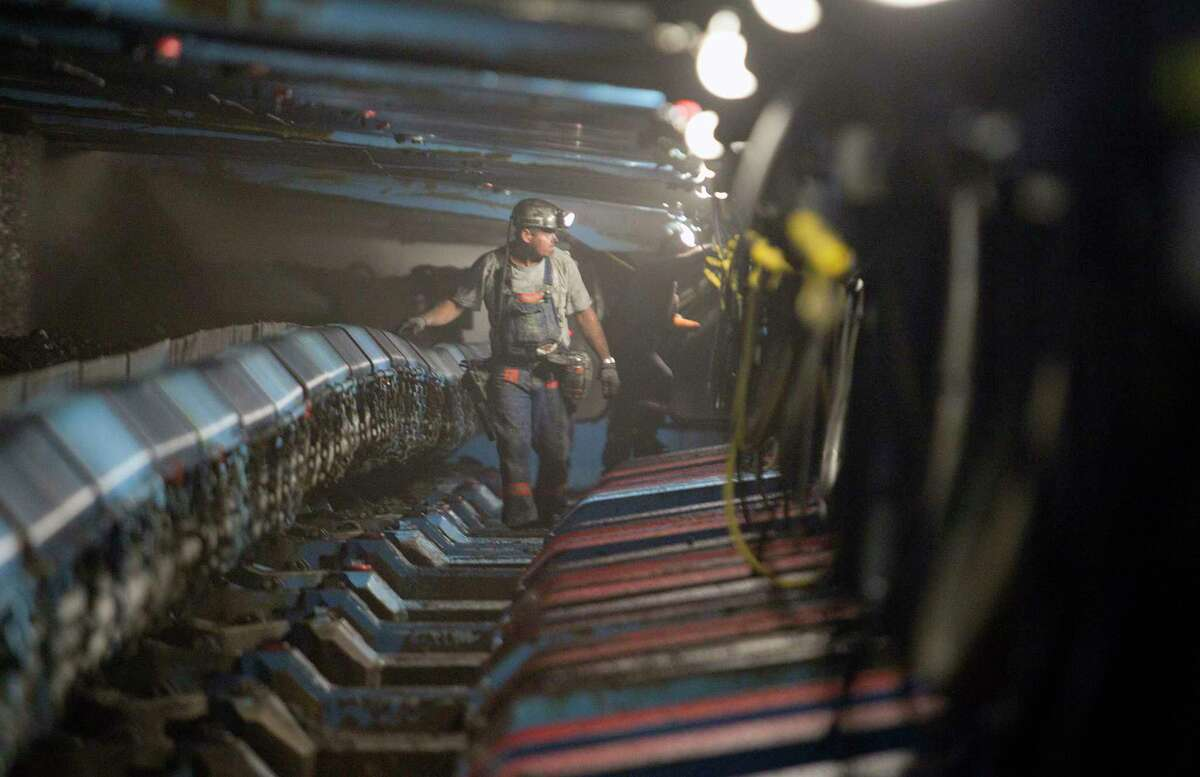 A miner passes hydraulic jacks next to a coal seam in the Pond Creek coal mine in Johnson City, Ill.