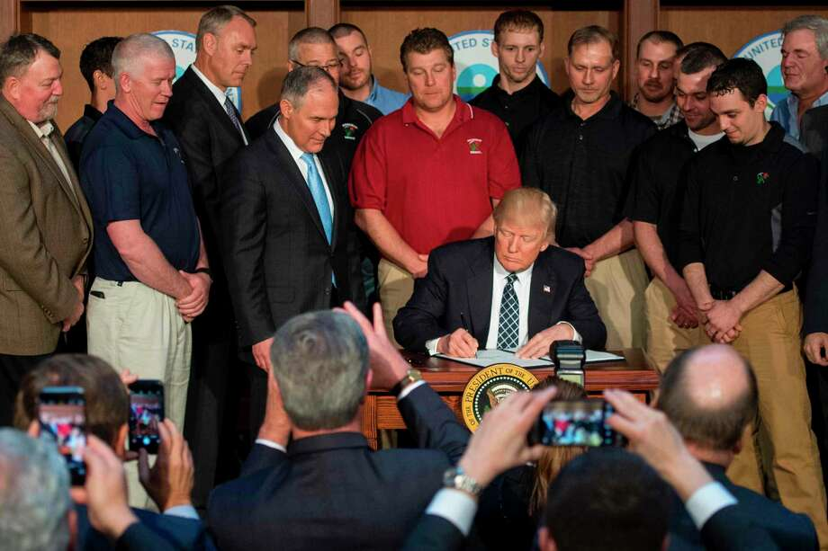 "Surrounded by miners from Rosebud Mining, US President Donald Trump (C) signs he Energy Independence Executive Order at the Environmental Protection Agency (EPA) Headquarters in Washington, DC, March 28, 2017. President Donald Trump claimed an end to the ""war on coal"" Tuesday, as he moved to roll back climate protections enacted by predecessor Barack Obama. / AFP PHOTO / JIM WATSONJIM WATSON/AFP/Getty Images Photo: JIM WATSON / AFP or licensors"