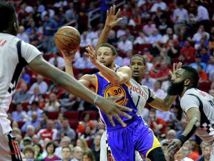 Golden State Warriors' Stephen Curry (30) dishes the ball between Houston Rockets' Clint Capela, Trevor Ariza (1) and James Harden (13) in the first half of an NBA basketball game in Houston, Sunday, March 28, 2017.