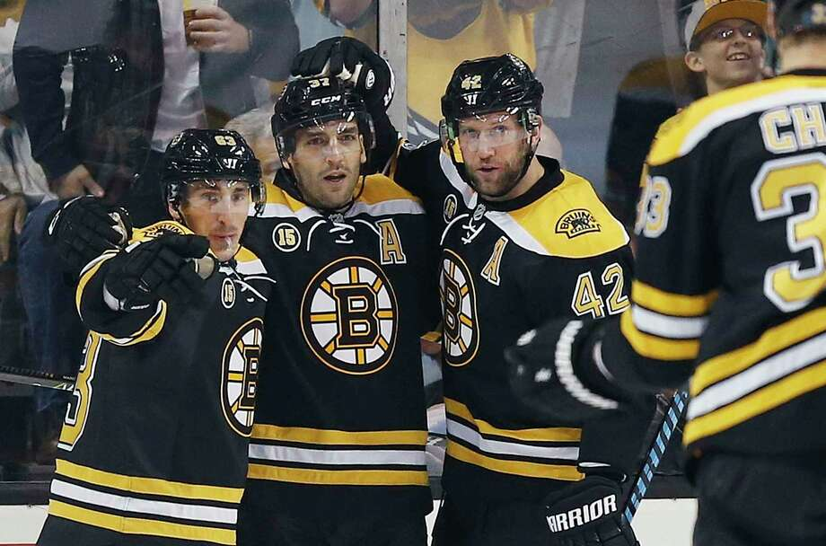 Boston Bruins' Patrice Bergeron (37) celebrates his goal with teammates Brad Marchand (63) and David Backes (42) during the first period of an NHL hockey game against the Nashville Predators in Boston, Tuesday, March 28, 2017. The Bruins on 4-1. (AP Photo/Michael Dwyer) ORG XMIT: MAMD109 Photo: Michael Dwyer / Copyright 2017 The Associated Press. All rights reserved.
