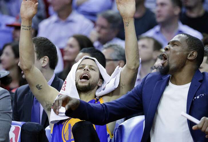 Golden State Warriors' Stephen Curry and Kevin Durant celebrate on the bench after a score in the second half of an NBA basketball game against the Houston Rockets in Houston, Tuesday, March 28, 2017. (AP Photo/Michael Wyke)