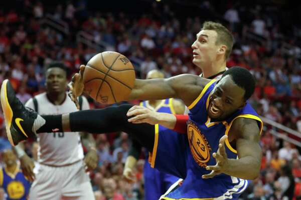 Warriors forward Draymond Green, right, goes sprawling in his fight for possession of the ball with Rockets forward Sam Dekker on Tuesday night at Toyota Center.