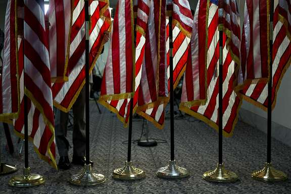 American flags are adjusted outside the Senate Judiciary Committee hearing room before the start of a confirmation hearing for Neil Gorsuch, U.S. Supreme Court nominee for U.S. President Donald Trump, not pictured, in Washington, D.C., U.S., on Monday, March 20, 2017. Gorsuch goes before a Senate committee as a heavy favorite, given Republican control, to win confirmation to a lifetime seat on the nations highest court. Photographer: Andrew Harrer/Bloomberg