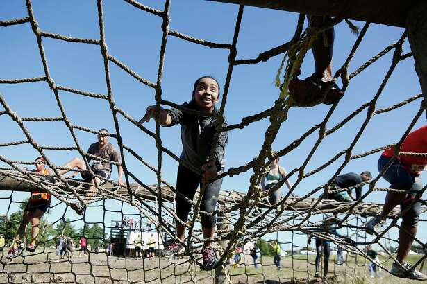 Dashers traverse an obstacle during the MIGHTY MUD DASH 5k challenge Sunday, Oct. 5, 2014, in Houston. The dash has 20& Military style obstacles. ( James Nielsen / Houston Chronicle )