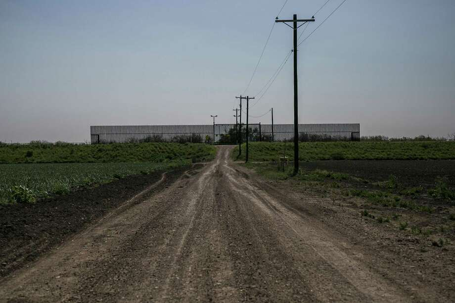 A section of border fence with a gate, bounded by smaller chainlink fence in Runn, Texas. The patchwork border fence along the Texas-Mexico border has created a nebulous and bizarre third space between countries: homes, cemeteries, hiking trails and farms that now lie south of the wall. Photo: Kelly West /TNS / Austin American-Statesman