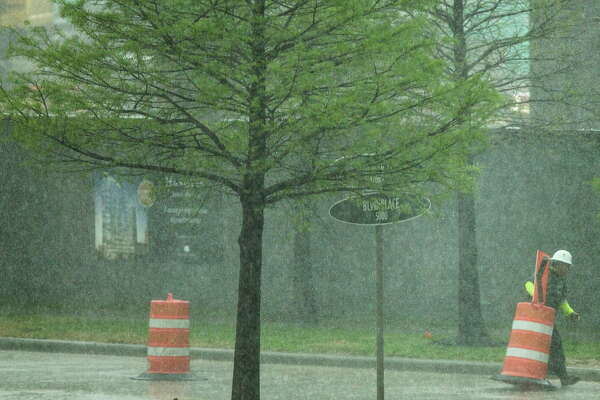 A construction worker moves a traffic barrel out of the street during a heavy downpour in the Galleria area on Wednesday, March 29, 2017, in Houston.