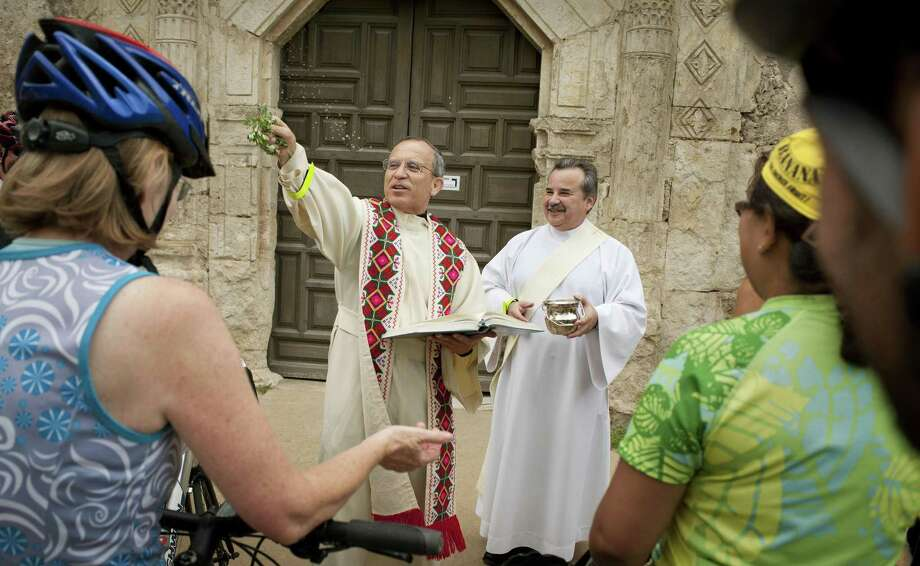 Father David Garcia blesses bicycles and riders with holy water, Sunday, May 20, 2012, at Mission Concepcion in San Antonio. (Darren Abate/Special to the Express-News) Photo: Darren Abate, FRL / Darren Abate/Special To The Expr