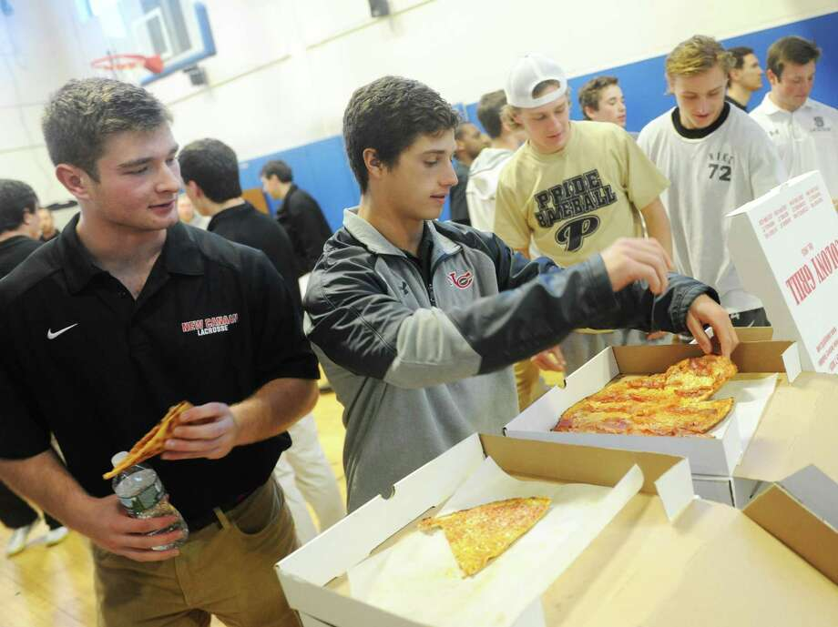 New Canaan's James Crovatto, left, and Jackson Appelt grab slices of pizza at the 2017 FCIAC Lacrosse Media Day at BlueStreak Sports Training in Stamford, Conn. Monday, March 27, 2017. Presented by the Ruden Report, the third-annual media day gave FCIAC lacrosse players and coaches from across Fairfield County the opportunity to hang out in a noncompetitive environment before kicking off the 2017 season. Photo: Tyler Sizemore / Hearst Connecticut Media / Greenwich Time