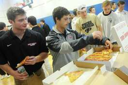 New Canaan's James Crovatto, left, and Jackson Appelt grab slices of pizza at the 2017 FCIAC Lacrosse Media Day at BlueStreak Sports Training in Stamford, Conn. Monday, March 27, 2017. Presented by the Ruden Report, the third-annual media day gave FCIAC lacrosse players and coaches from across Fairfield County the opportunity to hang out in a noncompetitive environment before kicking off the 2017 season.