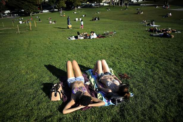 Nicole Viverito(R) of San Francisco and Sienna Moody of Oakland enjoy the warm weather and the chance to soak up some sun at Dolores Park in San Francisco, CA Monday March 11th, 2013.