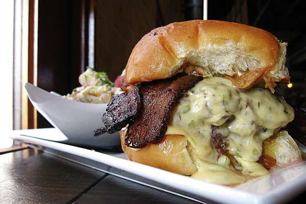 Boiler House's Jacky Treehorn Burger with bacon, foie gras peanut butter, poblano cheese and green tomato habanero jam, served with potato salad
