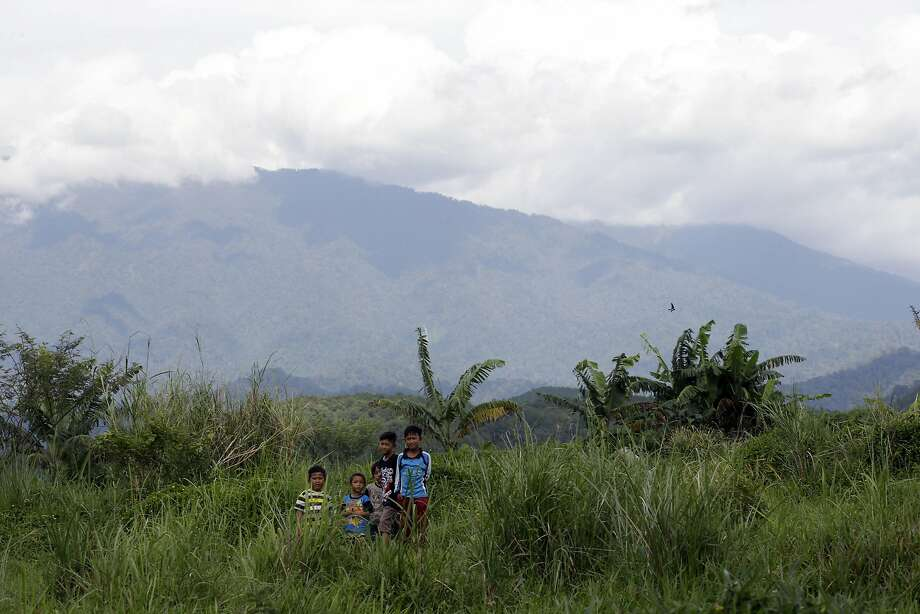 Children stand on a field near the Gunung Gede Pangrango National Park on Java island. Conservationists worry a Trump project will overwhelm the park. Photo: Tatan Syuflana, Associated Press