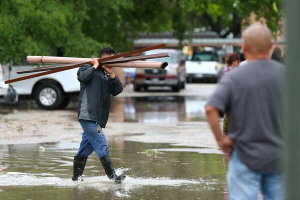 Simon Pineda carries debris caused by the severe weather at the 5900 Bissonnet Street apartment complex Wednesday, March 29, 2017, in Houston. ( Godofredo A. Vasquez / Houston Chronicle )