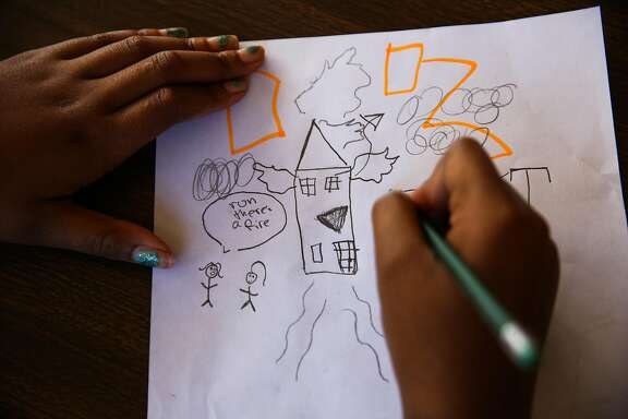 Evacuee Imani Smith, 12, draws a picture of the her experience escaping a fire that destroyed her home in an apartment building on San Pablo Ave. on Monday, March 27, 2017, in Oakland, Calif. At a makeshift  evacuation area for those who were displaced on 27th and Broadway, Imani's sister Naimah (not pictured) asked photographer Gabrielle Lurie for a paper and pen to draw her experience. Imani decided to also draw her experience as seen in the image.