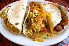 A trio of breakfast tacos on handmade flour tortillas, From left: Country sausage and egg, chilaquiles and weenies in salsa. From Los Campos Dos Hermanos on West Military Drive in San Antonio. For the 365 Days of Tacos series.