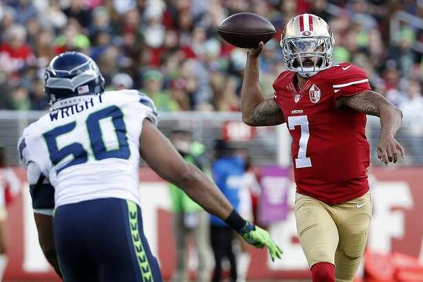 San Francisco 49ers quarterback Colin Kaepernick (7) passes against Seattle Seahawks outside linebacker K.J. Wright (50) during the first half of an NFL football game in Santa Clara, Calif., Sunday, Jan. 1, 2017. (AP Photo/Tony Avelar)