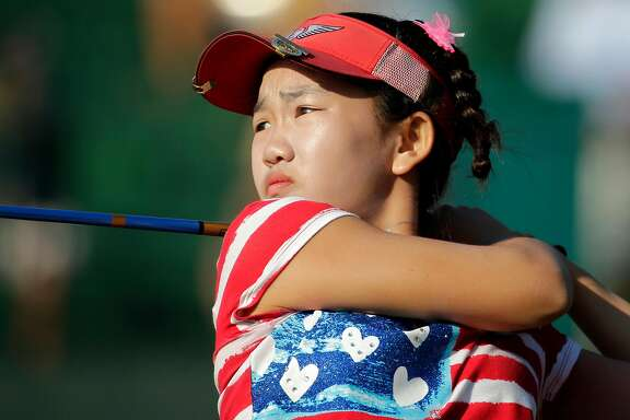 Lucy Li watches her tee shot on the 14th hole during the first round of the U.S. Women's Open golf tournament in Pinehurst, N.C., Thursday, June 19, 2014. (AP Photo/Chuck Burton)