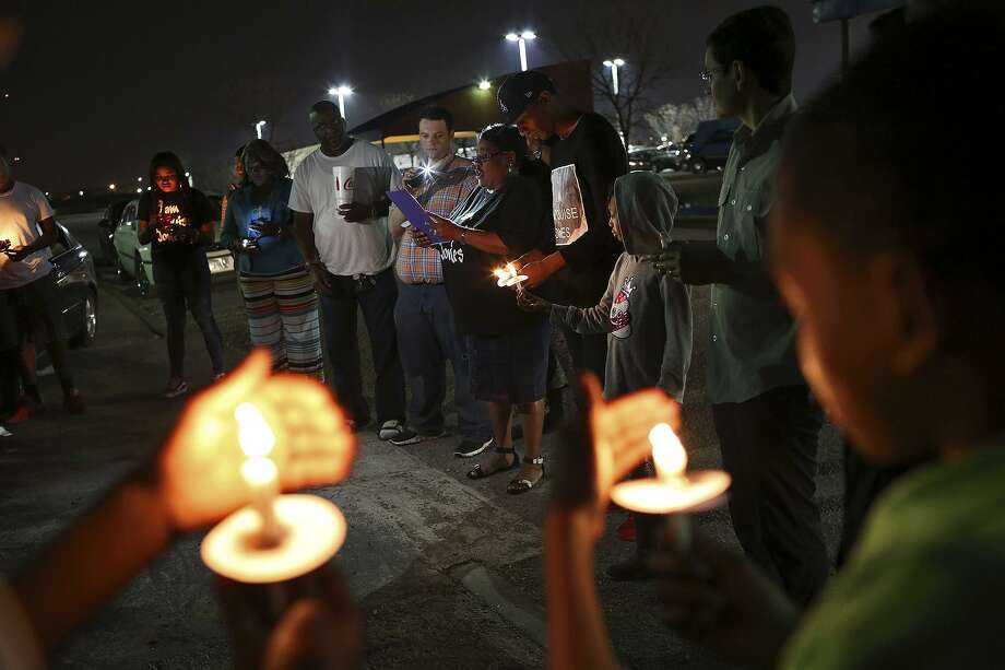 Debbie Bush, the aunt of Marquise Jones, center, reads a poem on behalf of Jones' mother who was out of town, during the vigil for the third anniversary of Jones' death outside Chacho's restaurant in San Antonio on Tuesday, Feb. 28, 2017. Also present are Jones' father, Blake Lamkin, left, and Mike Lowe, right, with SATX4. Photo: Lisa Krantz, STAFF / SAN ANTONIO EXPRESS-NEWS / SAN ANTONIO EXPRESS-NEWS