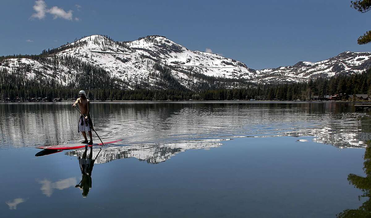 Mitch DeAngelis of Tahoe Donner mixes summer and winter as he paddles Donner Lake, Ca., on Tuesday June 7, 2011. Snow depth monitoring in nearby Soda Springs shows that is is the deepest snow at this date in the high elevations since records were begun in 1868 by the folks that built the Transcontinental Railroad.
