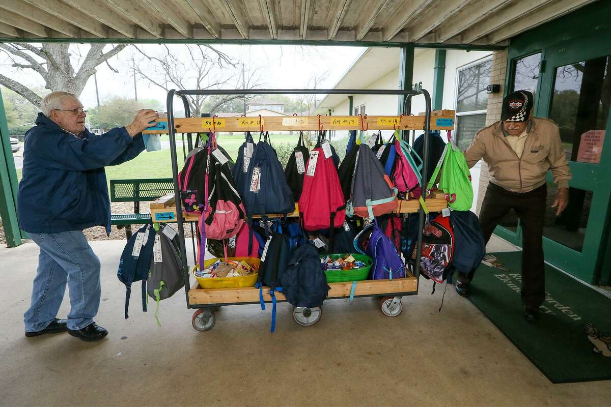 """Jim Lloyd (left) and George Atkinson take a transport cart loaded with backpacks from Universal City United Methodist Church into the adjacent Rose Garden Elementary School for distribution to students under """"Operation Backpack,"""" a program originated by the church working with Communites in Schools, on Thursday, March 9, 2017."""