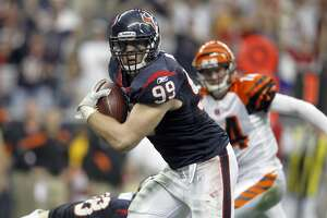 Houston Texans defensive end J.J. Watt (99) returns an interception 29 yards for a touchdown as Cincinnati Bengals quarterback Andy Dalton (14) gives chase to give the Texans the lead during the second quarter of an AFC wildcard playoff football game at Reliant Stadium on Saturday, Jan. 7, 2012, in Houston. ( Karen Warren / Houston Chronicle )