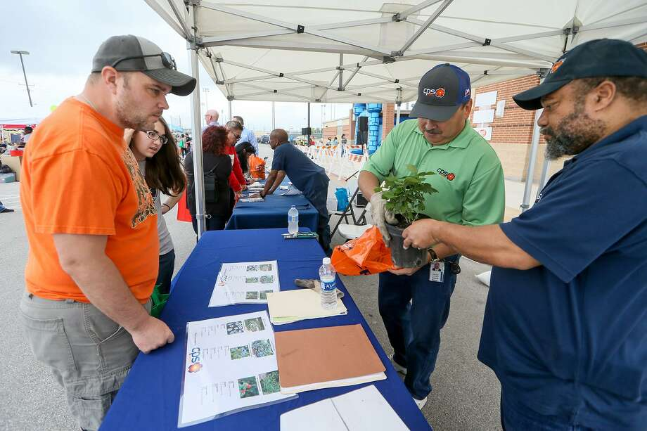 Willie Davis (right) and Roland Hinojosa with CPS Energy pick out a Turk's Cap plant to give to Christopher Harlan (left) and his daughter, Katelyn Harlan, 14, during the sixth annual Converse Goes Green at Rutledge Stadium on Saturday, March 18, 2017. CPS Energy also gave away free Blackfoot Daisy and Dwarf Plumbago plants to people at the event. Photo: Marvin Pfeiffer / San Antonio Express-News / Express-News 2017