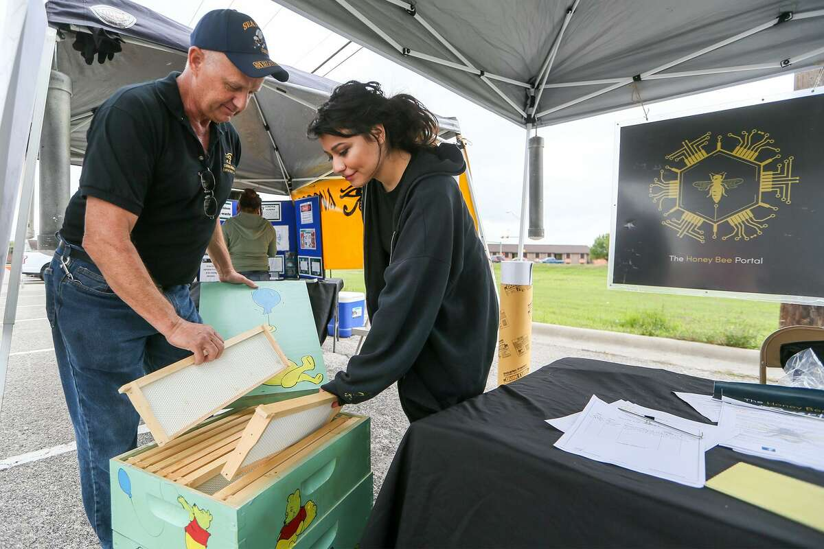 Vandell Norwood (left) and Savannah Quintana with the Urban Bee Keeping Group display the frames inside a bee hive during the sixth annual Converse Goes Green at Rutledge Stadium on Saturday, March 18, 2017.