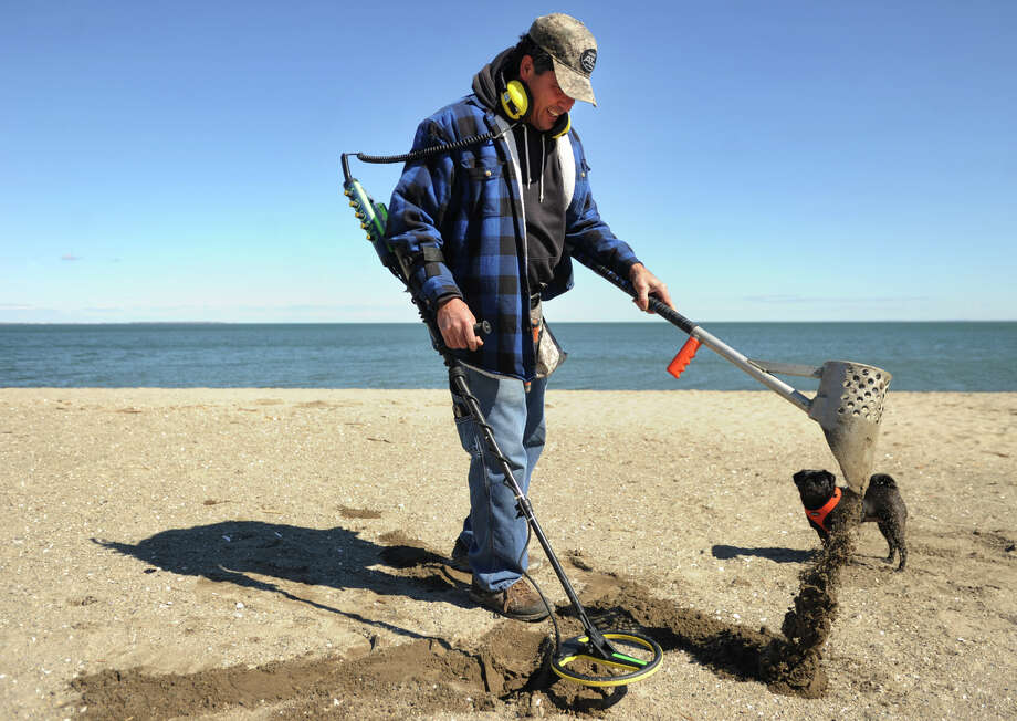 Tony Schell, of Fairfield, and his dog Chloe, take advantage of the sunny spring weather to dig for buried treasures at Penfield Beach in Fairfield, Conn. on Wednesday, March 29, 2017. Photo: Brian A. Pounds, Hearst Connecticut Media / Connecticut Post