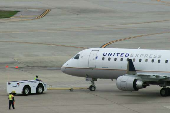 A United Express flight operated by Mesa Airlines is pushed back from its gate at Bush Intercontinental Airport in February 2017.