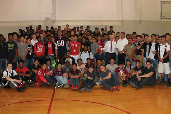 Cleveland High School's male athletes gather around Houston Texans' offensive lineman Tony Bergstrom at the end of his visit to the school on Wednesday, March 29.