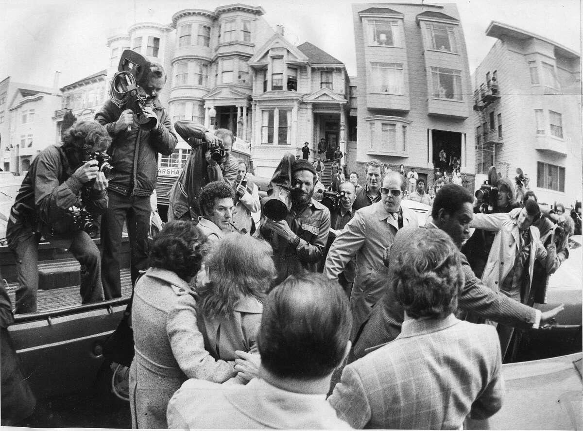 U.S. Marshalls hustle Patty Hearst back in the car after visit to 1827 Golden Gate apartment where she showed the judge and jury one of the closets in which she was imprisoned after being kidnaped by the SLA Photo ran 02/177/1976, p. 1