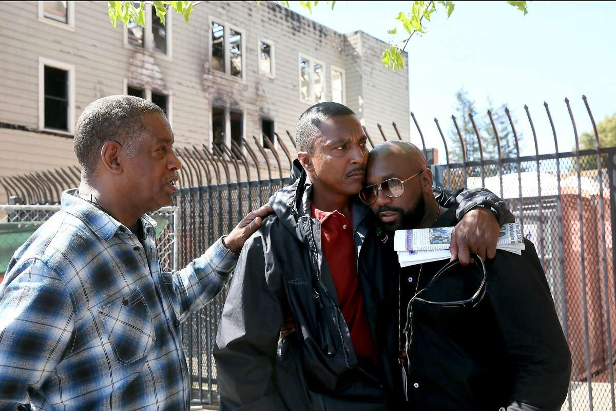Leandre Johnson, (center) who lost his wife Cassandra in the fire is comforted by his two brother-in-law's Romell Lee, (left) and Tywon Lee who lost their sister, at the scene of the fire along the 2500 block of San Pablo Ave. in Oakland, Ca., on Wed. March 29, 2017.