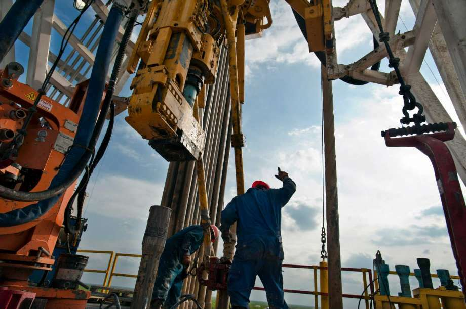 A crew works on a drilling rig in Webb County. Two recent reports point to an improved oil patch outlook.